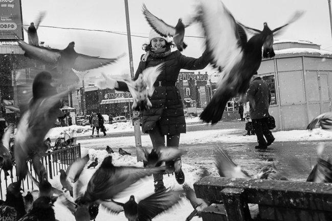 Репортажная фотография - девушка разгоняет голубей