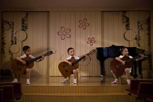 Pjongjang, severnokorejska dečica sviraju na priredbi u obdaništu Kjongsang