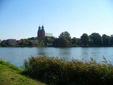 widok na archikatedrę gnieźnieńską znad jeziora jelonek, widoczne charakterystyczne wieże katedry