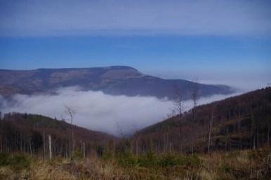 widok na najwyższy szczyt beskidu śląskiego skrzyczne i mgły w dolinie ze szlaku w okolicy muronki