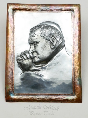 Repusowany wizerunek Jan Pawła II w blasze tytan-cynk. Rama miedziana. Wymiary razem z ramką 190 mm x 140 mm.