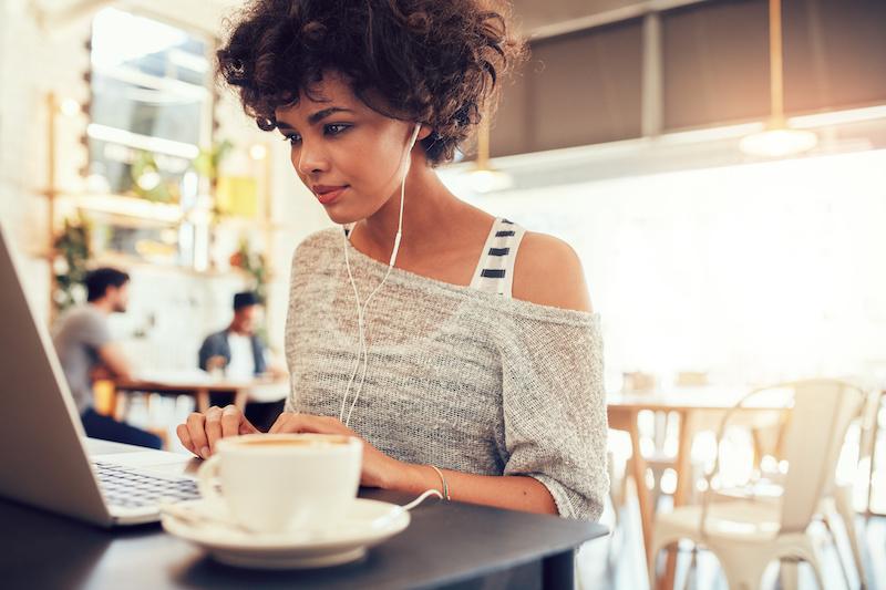 Modern woman using laptop at cafe.