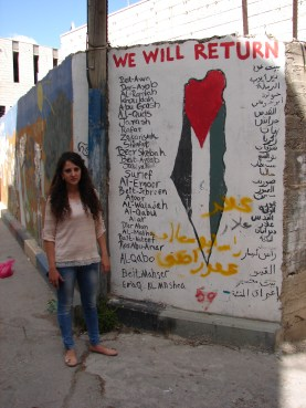 Shatha, our guide in Aida refugee camp, next to a mural listing the names of all the villages represented in the camp.