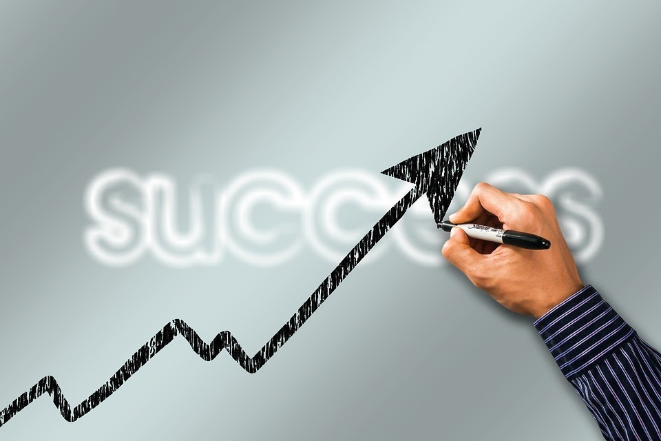 Hand drawing a line on a board with an arrow at the top. Success is written on the board.
