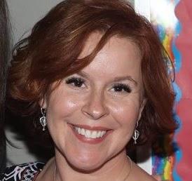Owner and Founder Pamela Furr smiling. Caucasian Female, bright smile, red hair, kind eyes.