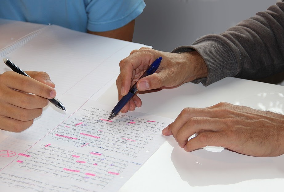 Expert tutor teaching student with marked up paper