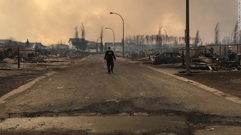 A Canadian Mountie surveys the devastation in Fort McMurray  (Photo: @RCMPAlberta) #ymmfire