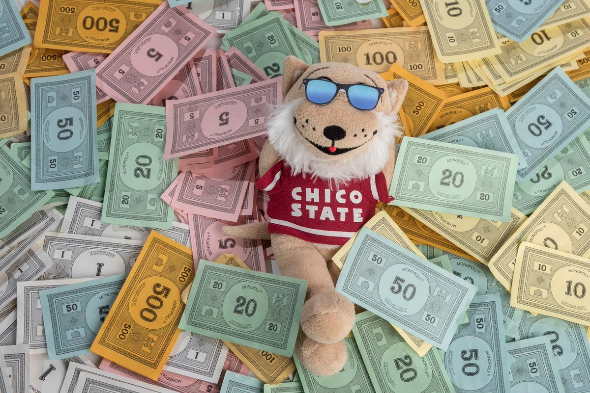 A doll of Willie the Wildcat, Chico State's mascot, relaxes in a pile of Monopoly money.