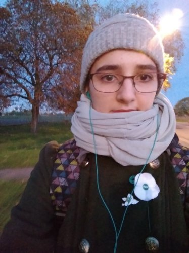 A selfie of a young person (me) wearing a dark green coat, a grey beanie, and a tightly wrapped light green snood. There is lens flare on the corner of the image, and I'm wearing a white poppy with the word 'peace' in the middle pinned to my chest.