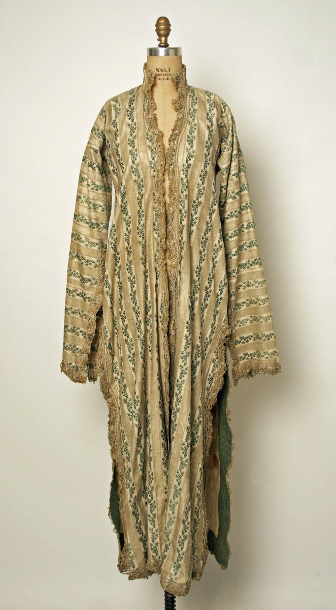 Ucetek Entari from Turkey, a kaftan with floral stripes in green and tan, bordered in lacy embroidery. From the Met museum.