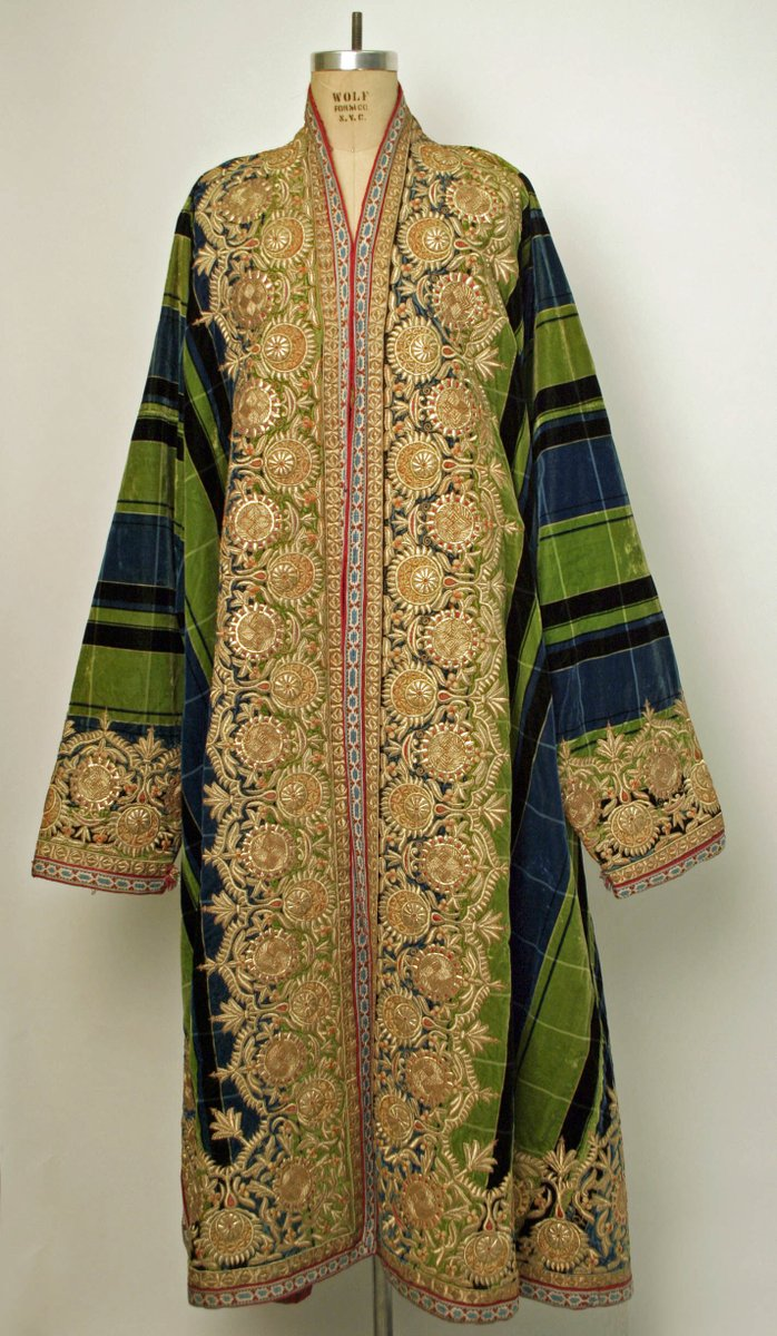 A striped and heavily embroidered kaftan style robe. The stripes are green, blue and black, and the thick embroidery is on the edges--all over the chest, hem, and cuffs.
