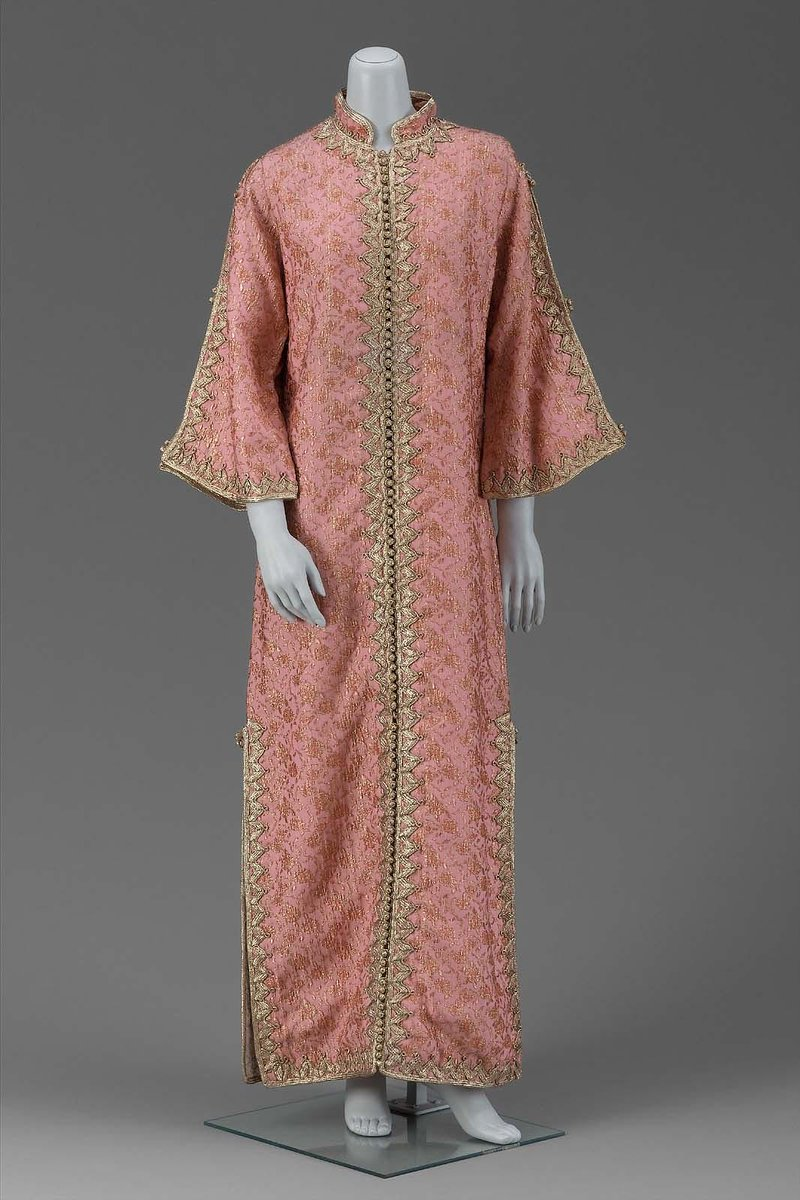 Robe of matelassé fabric woven with pink synthetic fibers and gold Lurex; trimmed with gold Lurex braid and lined with cream rayon; center front, button closure and stand-up collar. From the Boston MFA.