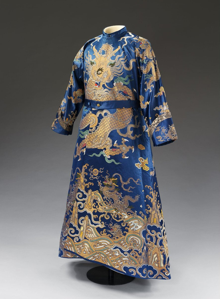 ©Victoria and Albert Museum, London - Man's banyan and sleeved waistcoat made from woven-to-shape lengths of a royal blue silk Imperial Dragon robe, brocaded with gold filé, coloured silk floss and peacock feathers in a design with nine dragons and stylised landscape borders. The robe side opening was stitched closed, and the centre-front seam unpicked to make the banyan. The under-front of the robe became the waistcoat fronts, with areas of brocaded silk at their hems. The plain satin around the brocaded shapes was cut and pieced to make the sleeves, back of the waistcoat, belt and pockets for the banyan. The waistcoat is lined with fine bleached linen.
