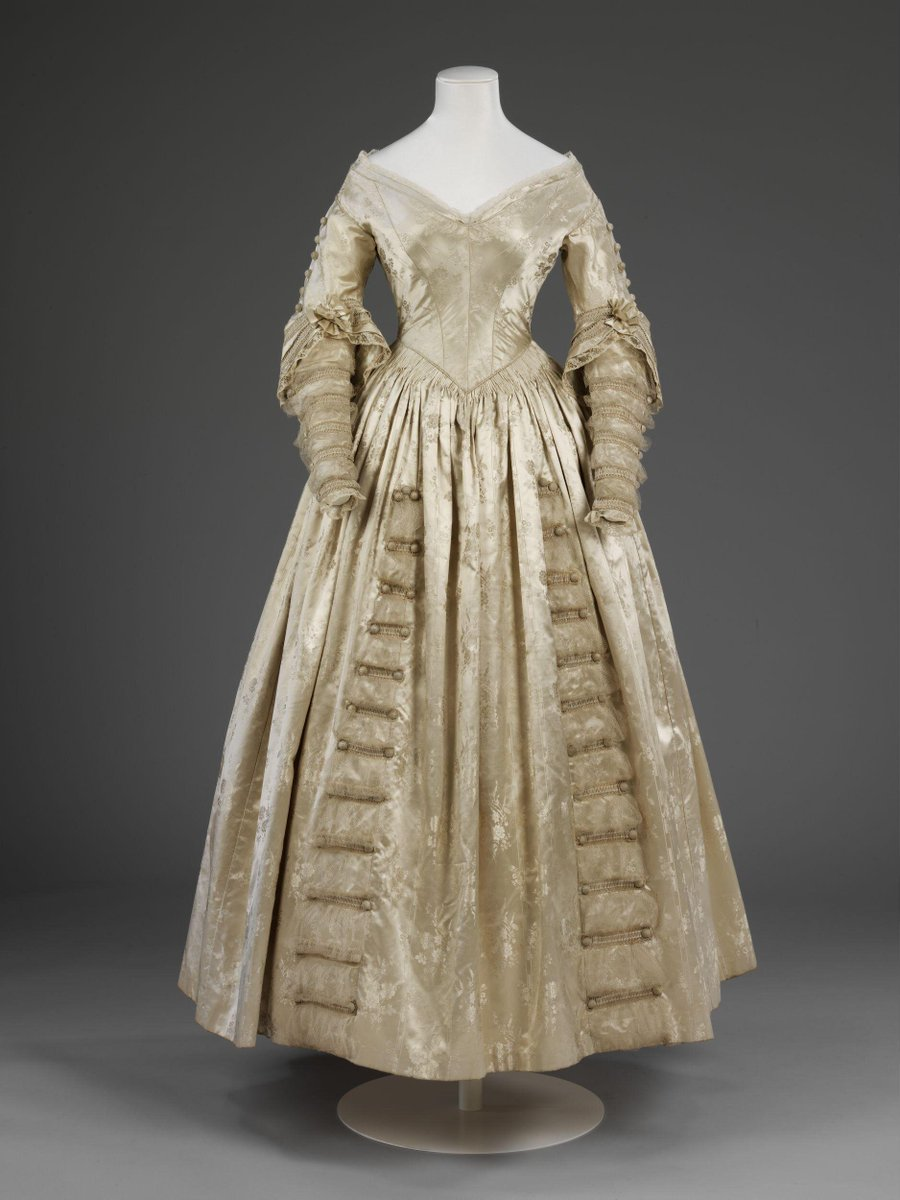 This wedding dress was worn in 1841 by an unknown but fashionable bride. The period 1838-1841 was a transitional period during which full, puffed sleeves and short-waisted bodices gave way to a slimmer, elongated silhouette, as exemplified by this gown's long-waisted, form-fitting bodice with narrow sleeves. The sleeves and skirt are trimmed with gathered tulle and applied strips of braid and buttons. The cream silk satin fabric is figured with flower-baskets, stripes and floral sprays.  This was an extremely sophisticated dress for 1841. The low-cut neckline is an especially modish feature which appears in fashion plates of the decade. Many nineteenth century brides wore matching capes or pelerines over low-cut bodices, or covered exposed necks and upper chests with high-necked chemisettes. ©Victoria and Albert Museum, London