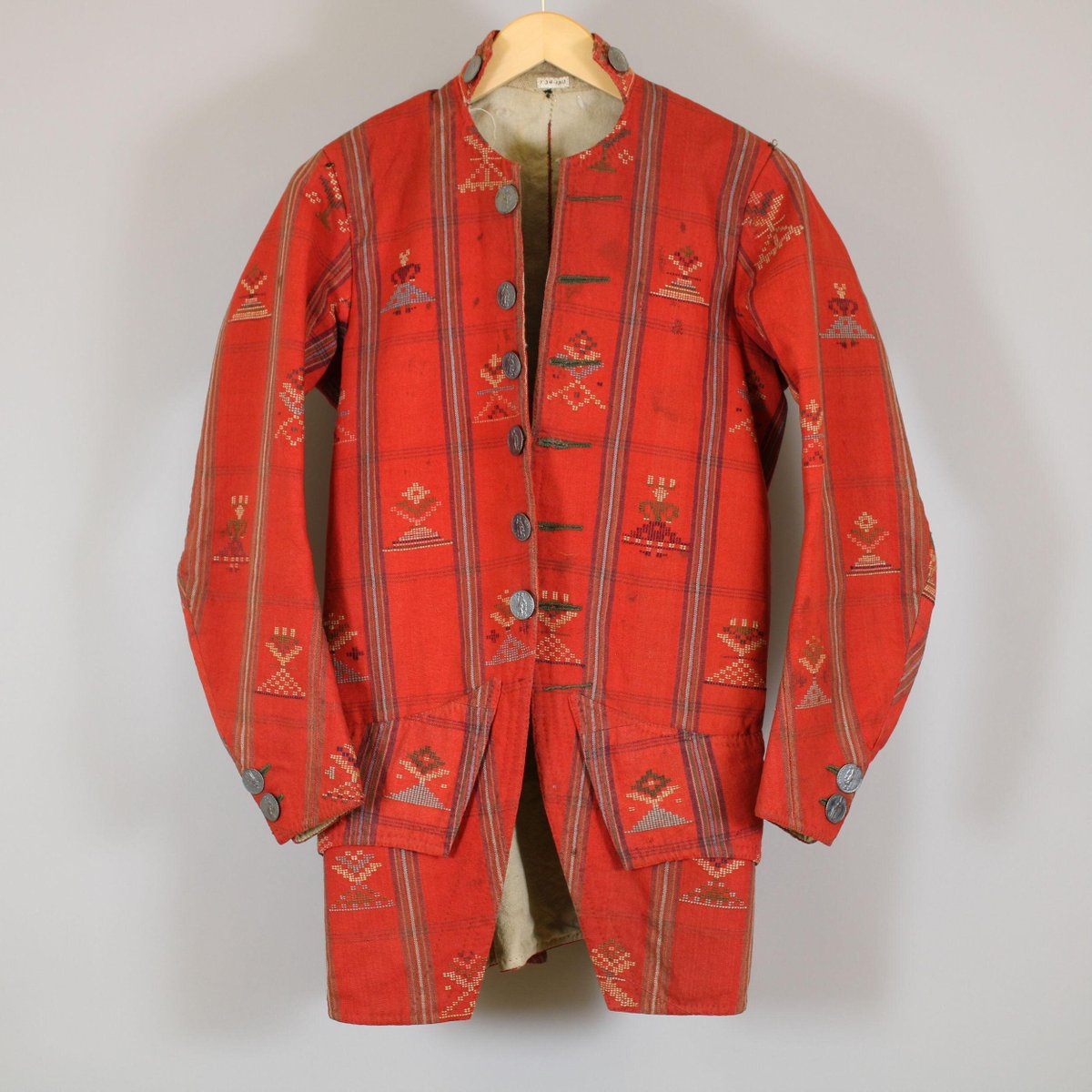 Bridegroom's jacket of red woollen cloth, woven in a pattern of stripes and further embroidered with coloured wools. Part of a Norwegian bridegroom's costume purchased by the donor in 1865 from the original owner. The jacket is skirted and slightly cut away in front, with long narrow sleeves. The pattern is a plaid, partly filled with conventional figures supposed to represent the bride, trees, and floral ornament, repeated diagonally within oblong compartments formed by the plaid. White wool lines the jacket. © V&A museum