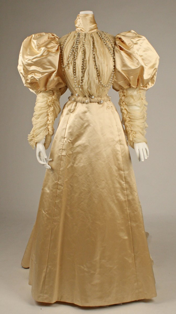 """An ivory gown in satin with long strands of pearls on the bodice. """"Mutton leg"""" sleeves of big poofs, a narrow waist, and a high neck. Minimal flare. Draped lace ruching on the bodice and lower sleeves. From the Met."""