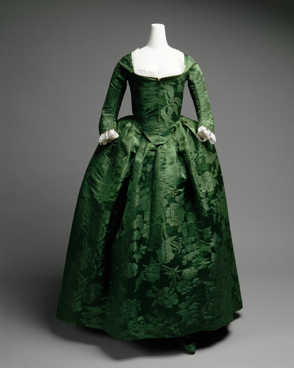 """This dress is considerably less gaudy than continental and English clothing of the period. Yet, it is not lacking in sumptuousness. Rather, the green Spitalfields damask, attributed to Anna Maria Garthwaite about 1743-45, is richly displayed. The Costume Institute acquired this dress in 1994, knowing that it would be in the Museum's exhibition """"John Singleton Copley's America."""" It has since appeared in our show """"The Ceaseless Century."""" One could argue that the relative simplicity engenders more delight in the dress's inherent voluptuousness. Generations later, it was said that Boston ladies waited a year before breaking out their new Paris finery from Worth; perhaps the American sensibility in luxury goods is slow and deliberate. The outfit includes matching shoes. Met Museum, Public Domain."""