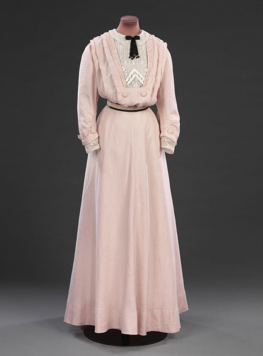 Pale rose pink linen day dress with a gilet fronted bodice and sleeve ends of embroidered striped net mounted on the top of white lawn lining. Covered linen button details to the bodice and the back of skirt, fullness in back. Collar embroidered with rouleaux braid, and a black satin ribbon bow at the neck. ©Victoria and Albert Museum, London