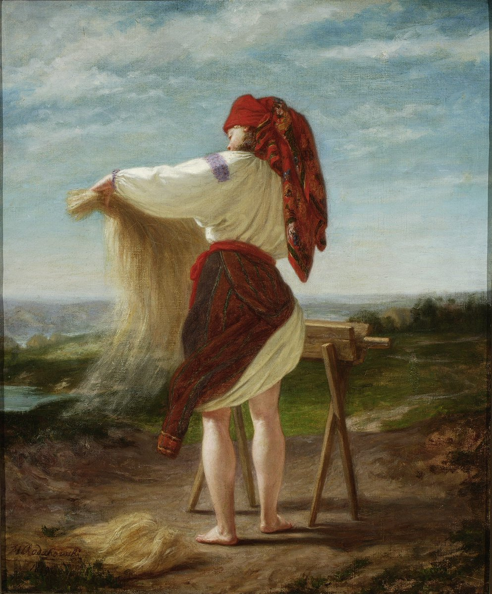 A harvester in traditional embroidered linen with a long thatch of flax in their arms.