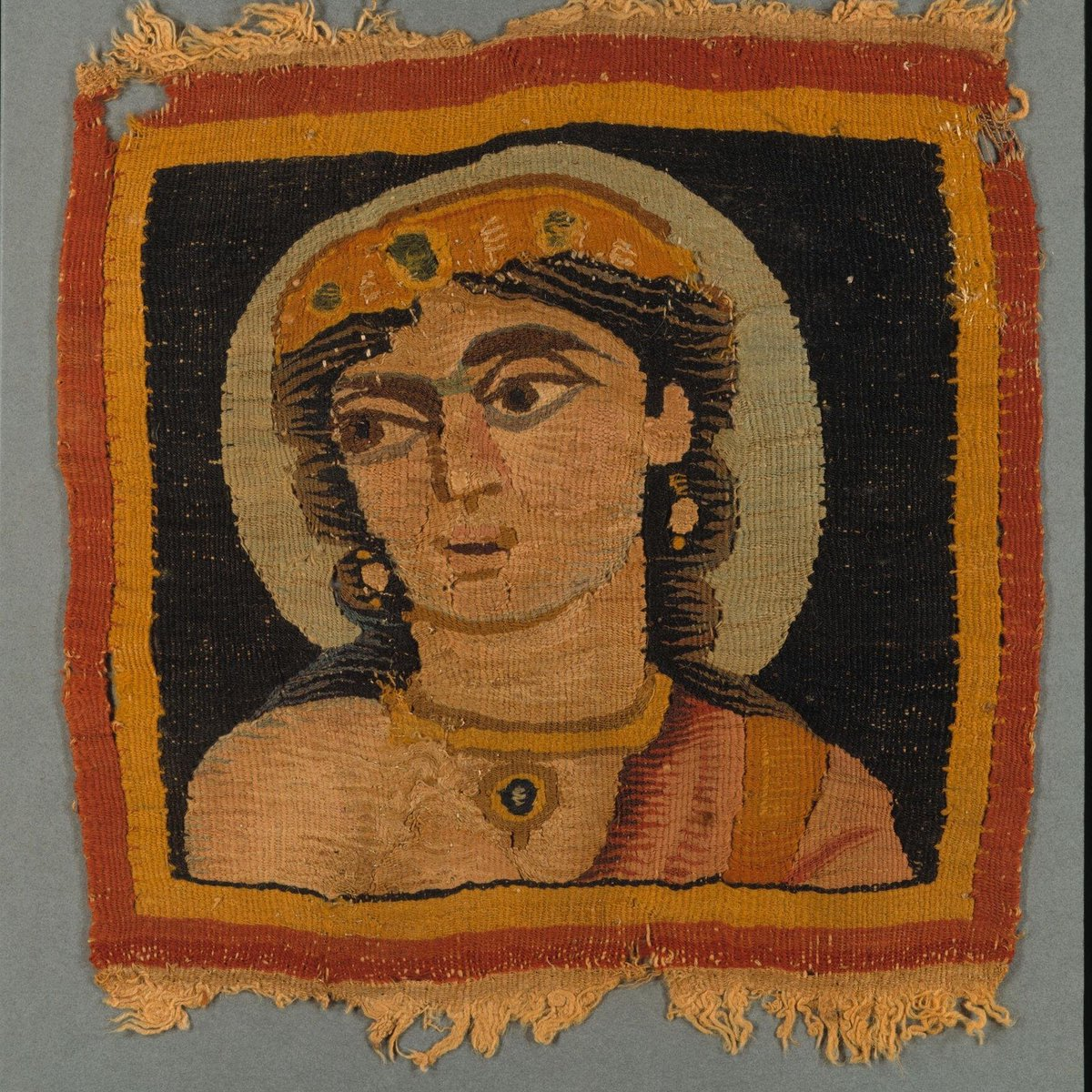 ©Victoria & Albert Museum, London - Square panel with portrait bust, almost certainly Aphrodite (Venus), appliqué from a tunic or more likely a furnishing textile. Wool with small quantities of linen, tapestry weave.  The woman is wearing a jewelled diadem, earrings and necklace with pendant. She wears a red garment over the left shoulder, and has a pale green halo. Plain red and yellow border.
