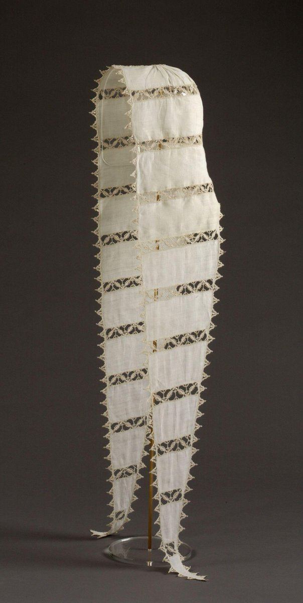 ©Victoria and Albert Museum, London - Coif of white linen gathered into a small needle lace roundel at the top, and with very long lappets which are integral and which taper gradually to a point. Decorated with horizontal bands of needle lace in a pattern of small open squares, each one containing a motif arranged diagonally, to give a chevron effect. Edged with small triangular needle lace motifs, each one finished off with a tiny trefoil.