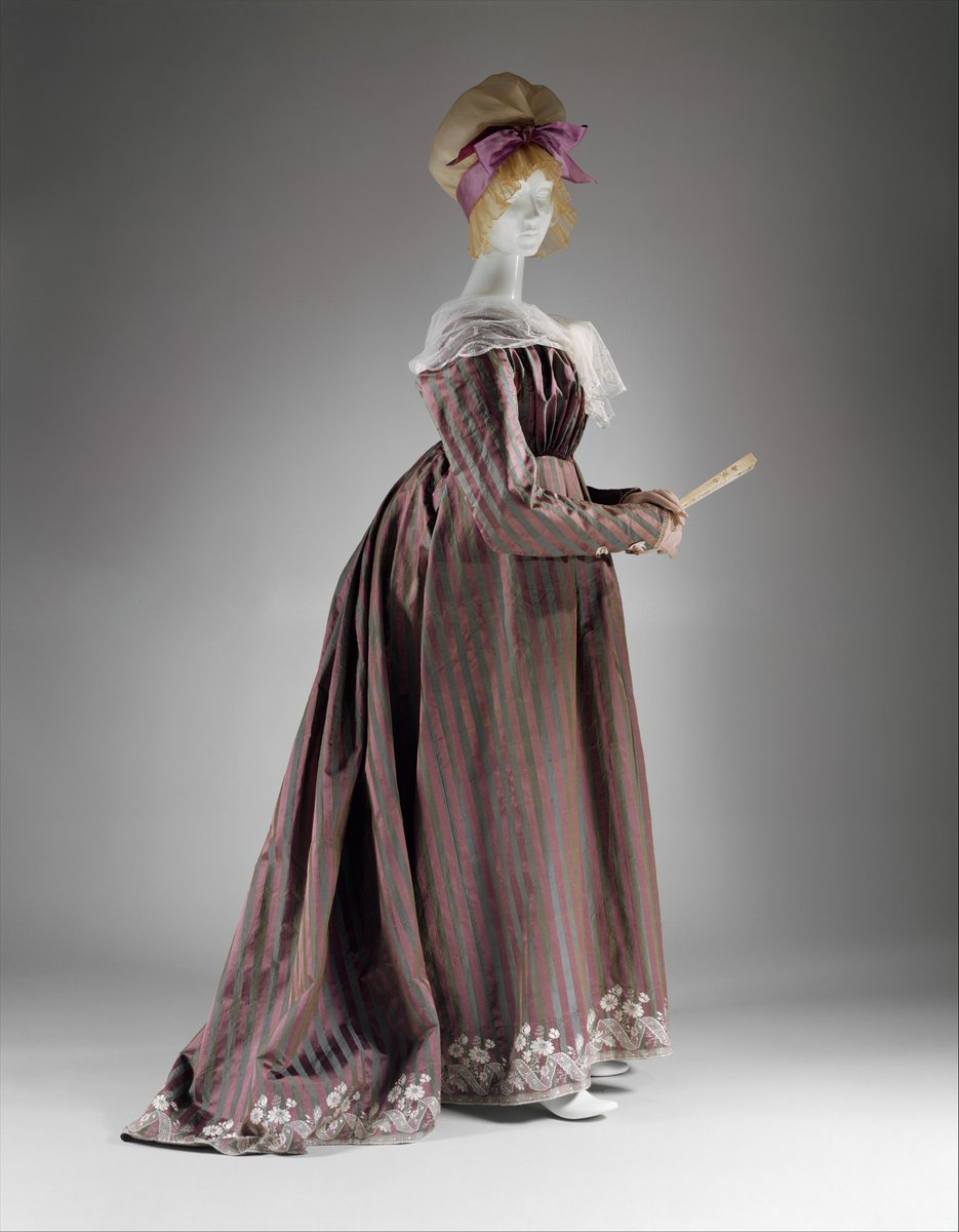 By the 1790s, the structure of clothing was undergoing dramatic change. This afternoon dress in the form of a round gown steadfastly keeps up appearances and can pass for eighteenth-century opulence, especially in its colors and textile richness. But the high-waisted dress, spencer, corset, and separate sleeves constitute a new anatomy, one that anticipates the century to come. This shape would be renewed in the 1880s and 1890s, as one fin de siècle recapitulated the preceeding fin de siècle. Met Museum, public domain.