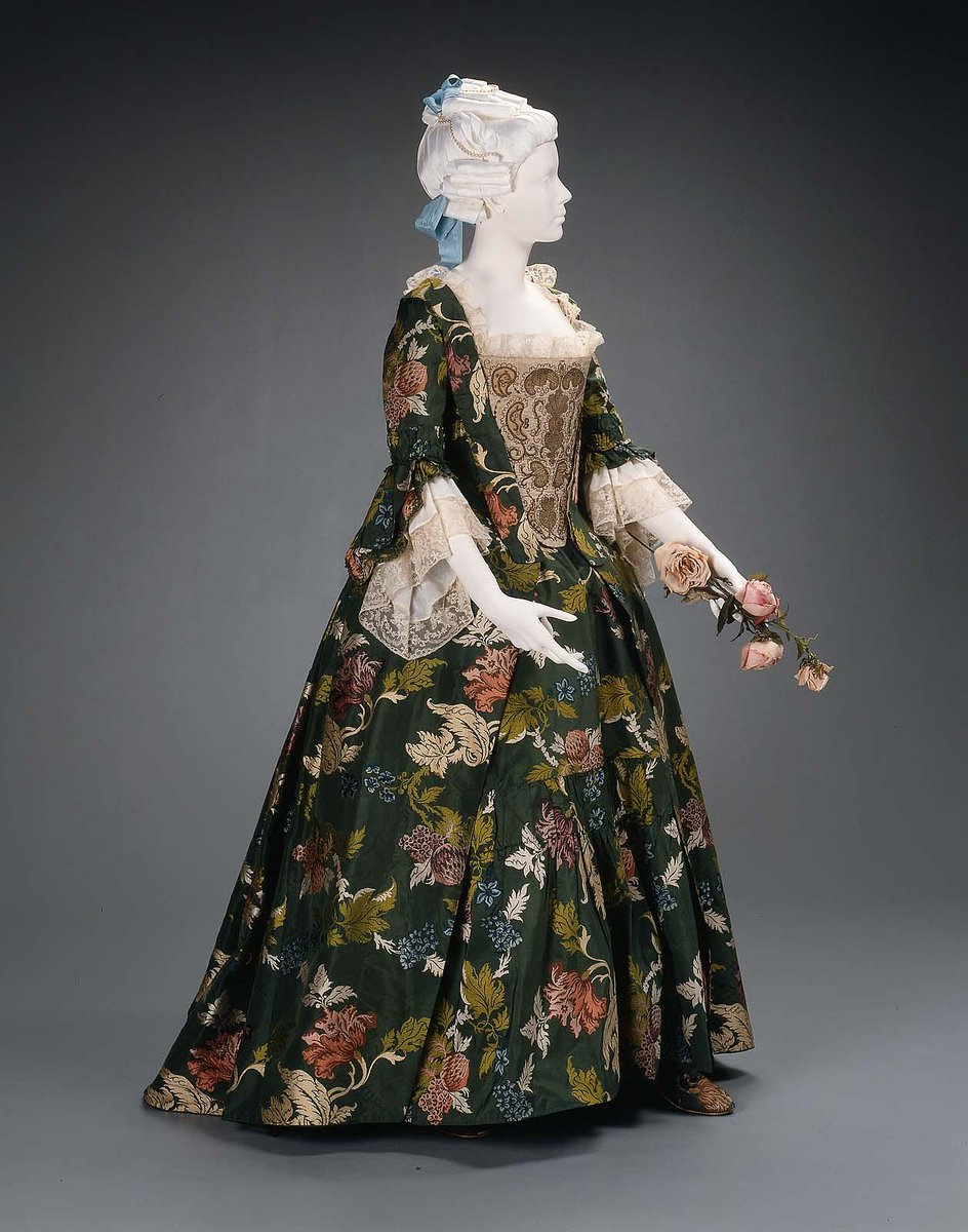 Remodeled 1763. Silk: England (Spitalfields), design about 1740. Dark green silk with polychrome brocaded design of flowers, leaves, branches and fruit. Mid-18th century linen bobbin lace stitched inside sleeve flounces and around neck. Open robe à l'anglaise and matching petticoat with deep flounce. Believed to have been worn by Mary Waters of Salem at her marriage to Anthony Sigourney of Boston in 1740. Also worn by their daughter, also named Mary Waters, for her marriage to James Butler in 1763. (Worn with 1990.514a, b). Condition: Petticoat good but fragile. Over dress (robe): good condition; left shoulder seam unstitched, back neck edge extremely worn. Boston MFA.