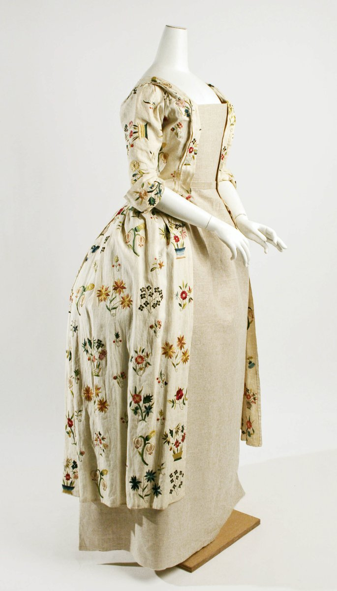 Linen gowns, plain versions of contemporary dress, were popular with gentlewomen for morning wear in the English countryside. These gowns were very sensible, as they could be laundered often and still retain a fresh appearance. They were often decorated with embroidery, usually stitched by the wearer herself. Embroidery was considered a gentle, feminine occupation for ladies of all classes of society. The lively floral embroidery on this day dress was probably done from a ready-made pattern, although the embroiderer has individualized the floral bouquets.