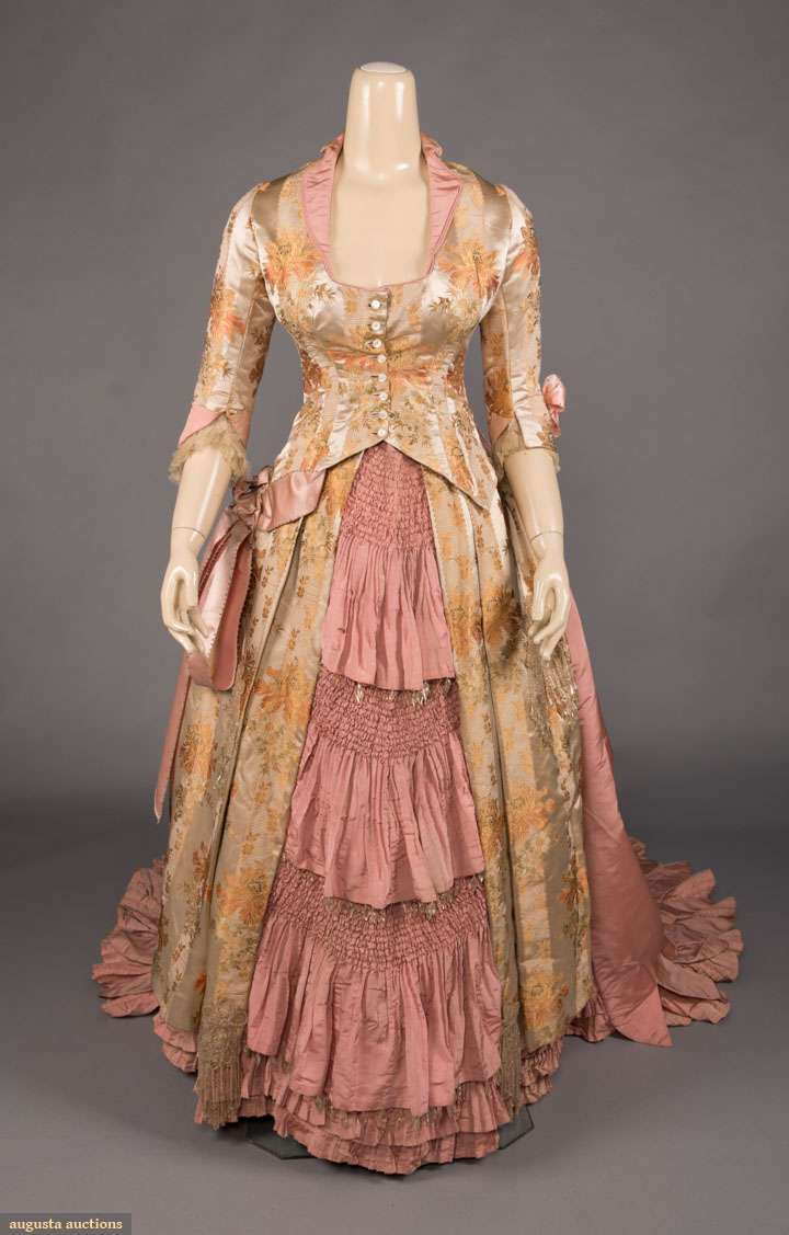 """2-pc 1880s gown in pink faille & brocaded oyster satin w/ poppy motif in orange & green, crystal beaded passementeries at front, blue & white beads on pink bow accents, trained, B 35"""", W 25"""", Bodice L 20"""", Skirt L 40""""-72"""", (cuffs damaged, skirt dirty w/ some pinholes, crystals added?, possibly altered)"""