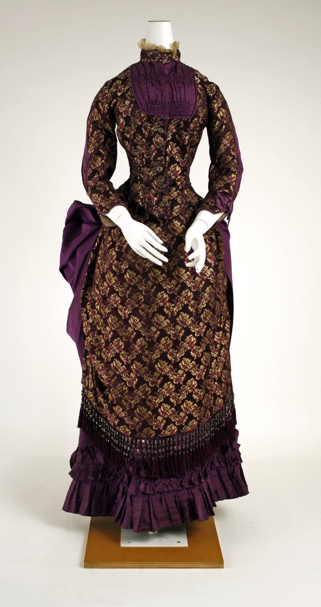 A purple brocaded gown with a high bustle and pleating at the collar and hemline. The edge of a large bow/bustle can be seen at the back. The brocade looks almost like a jacquard, but it's done in gold on a deep purple field. Long sleeves, high neck. Lace collar.