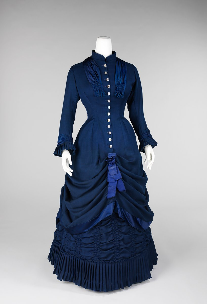 A blue walking gown in silk, with a row of white buttons, and lots of drapery (almost like a stage curtain). Lots of pleats at the bottom. High collar. Almost a suit-like silhouette.