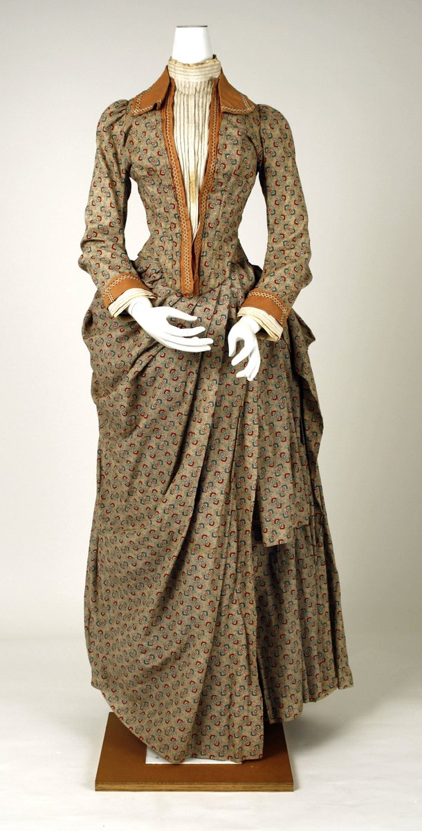 A tan walking dress from France, with a chintz pattern (calico). Orange piping on the collar, down the lapel, and the cuffs. Creme shirt underneath. Draped skirts.
