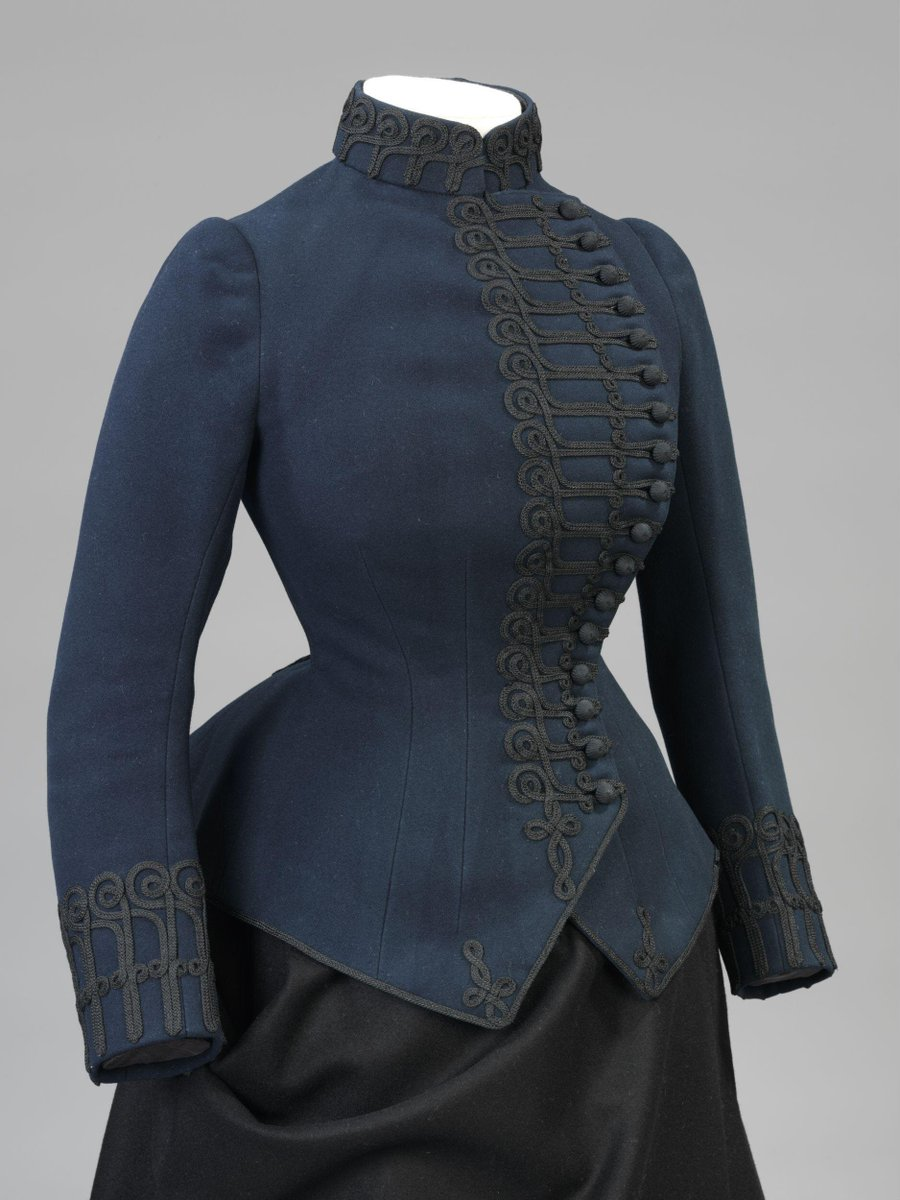 ©Victoria and Albert Museum, London - Description  Woman's riding jacket of navy blue flannel trimmed with mohair and lined with sateen. Fastened with hooks and eyes beneath the ornamental loop and button fastening. Braid.