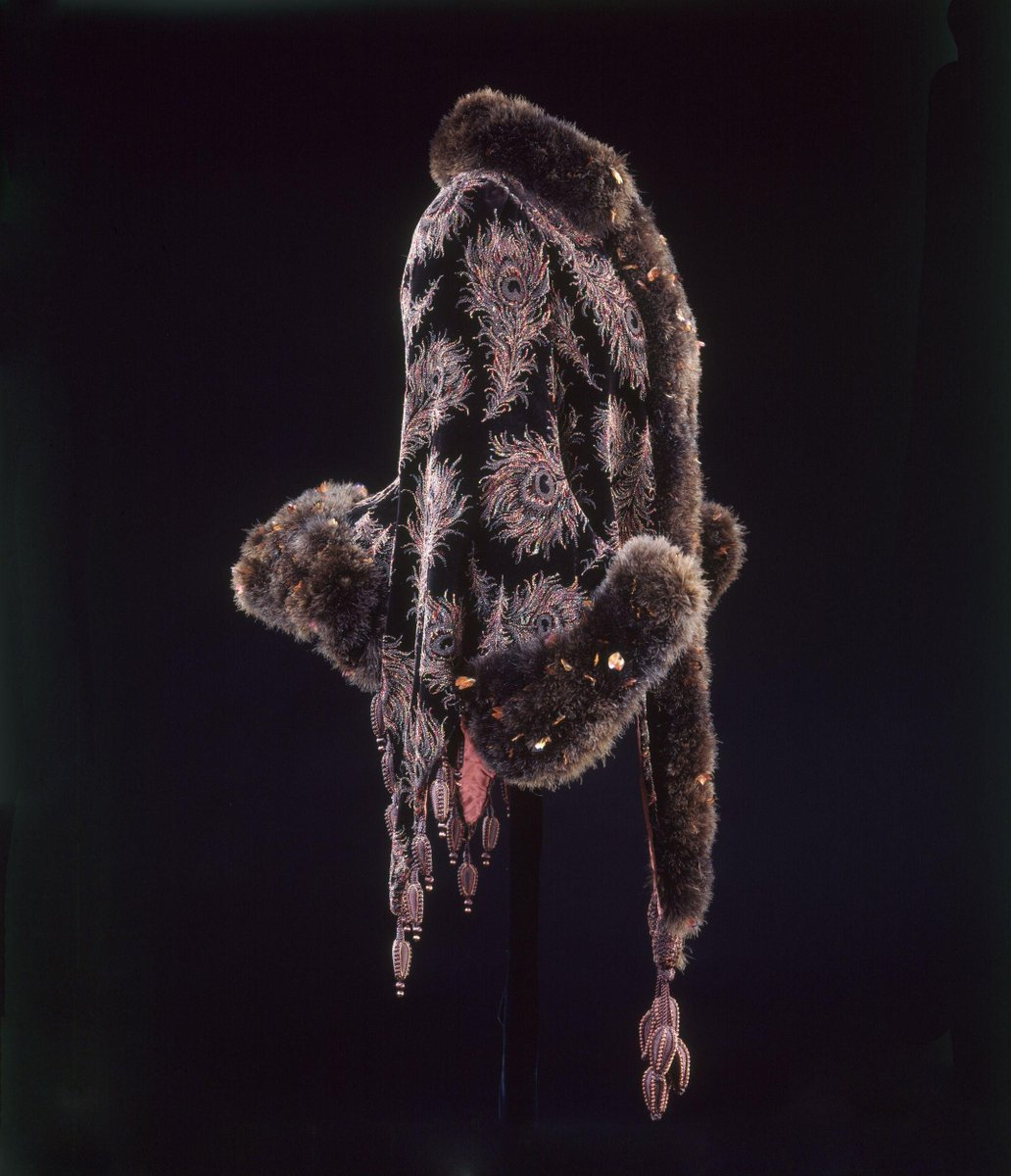 ©Victoria and Albert Museum, London - Dolman mantle of cut and uncut velvet with a feather trim and braided pendants tassels for decoration. Peacock feathers were a popular design motif in the 1860s to 1880s. Marabou trimming, obtained from the downy underwing feathers of the marabou stork became particularly fashionable in the second half of the 19th century. These birds were native to most part of the southern two thirds of Africa. Their downy feathers could be dyed any colour required and fashioned into long ropes of luxurious trimming, almost fur-like in appearance, as illustrated on this garment.