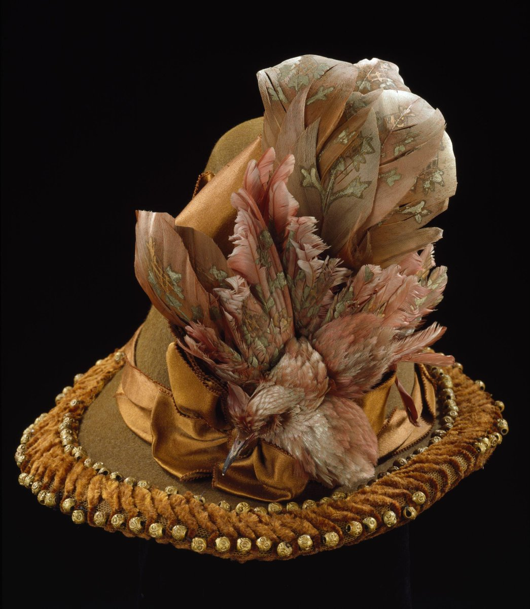 ©Victoria & Albert Museum, London - Brown felt trimmed hat, high crowned, with a narrow brim with feather and painted wooden bead decorations. Mounted with a specimen of a painted bird. With silk chenille and silk ribbons.