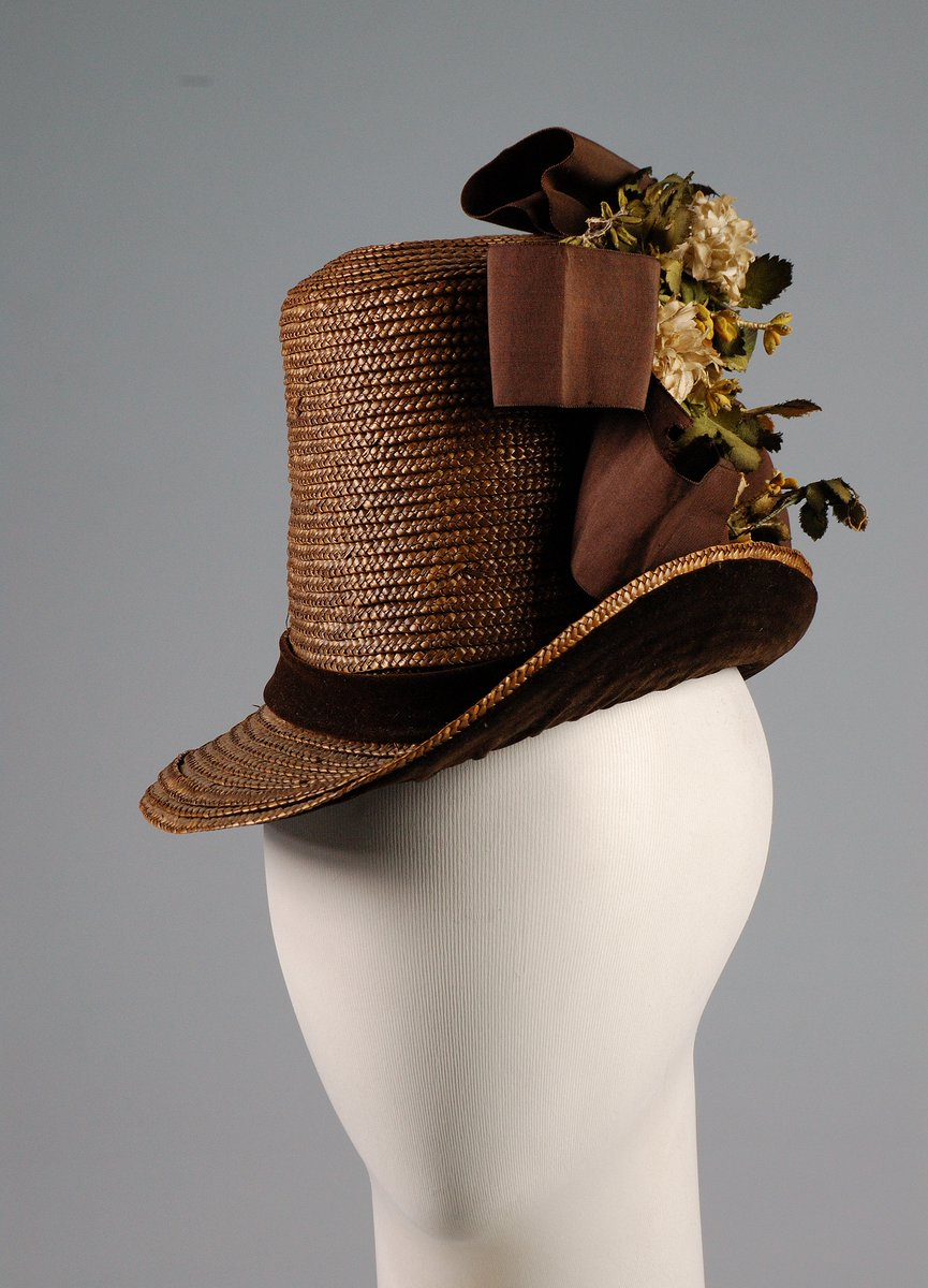 A brown straw tophat with a floral spray and brown bow, velvet ribbon on the brim, and a tilt to the side. Met museum, public domain.