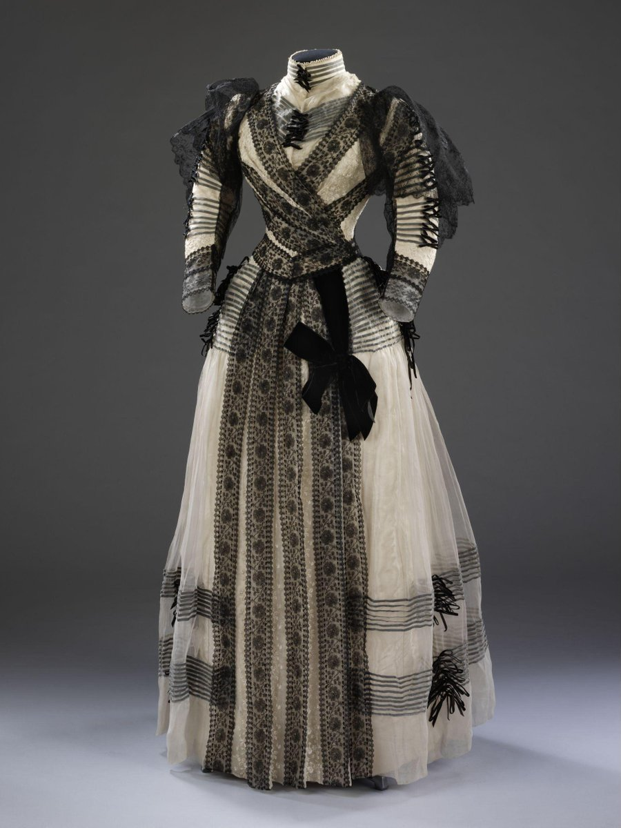 ©Victoria and Albert Museum, London - Formal day jacket bodice and skirt constructed from ivory coloured figured silk overlaid with chiffon encasing strips of black velvet ribbon, with bands of black machine lace, and with a panel of vertically striped black and ivory velvet at the centre back forming a bustle shape. Stitch marks suggest that there may have been an additional panel of lace or drapery applied over the back of the dress. Probably a half-mourning dress.