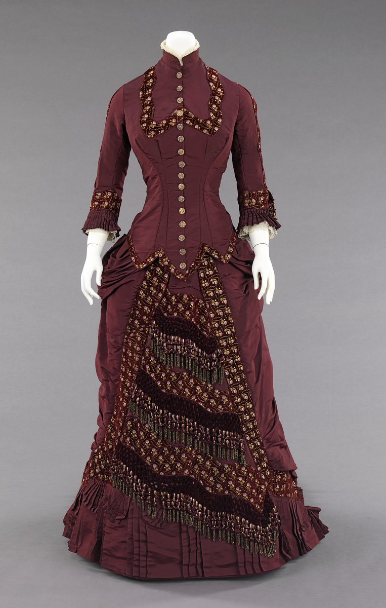 From the Met description: This dress belonged to Amelia Beard Hollenback (1844-1918), wife of the prominent financier and philanthropist John Welles Hollenback (1835-1927). In 1874, the Hollenback family settled in the neighborhood of Clinton Hill in Brooklyn. In the 19th century, Brooklyn became a metropolitan center with numerous affluent neighborhoods and a thriving downtown shopping district to fulfill. This dress, like many of the garments in Hollenback gift, was most likely custom-made by a Brooklyn-based dressmaker. The elaborate button and tassel decorations, the overall cohesiveness of design and the high quality of this stylish dress are a testament to the craftsmanship and great attention to detail carried out by American dressmakers at this time.