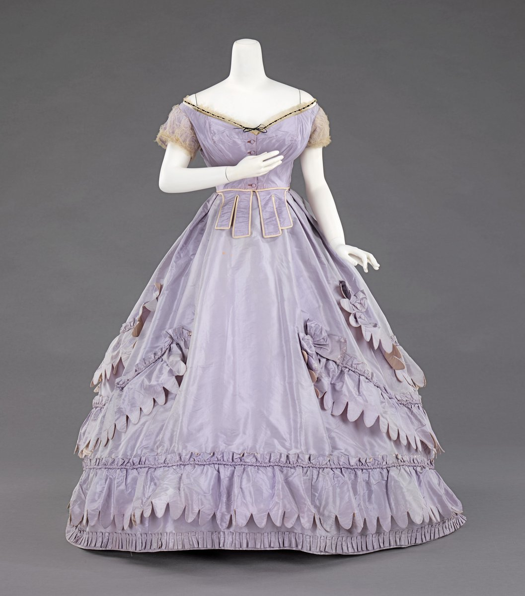 A lilac-hued gown with scalloped edges and a typical dropped shoulder design, lace cap-sleeves, and layer cake style. Narrow waist, darts at the waist as well, trimmed in yellow. But there are lots of little things happening all over the place that make it rather exceptional. Met Museum, public domain.