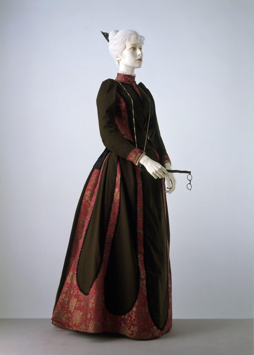 ©Victoria and Albert Museum, London - Day dress consisting of a bodice and skirt of dark green wool and red-ground silk brocade with a floral pattern. The bodice is waist-length, panelled with satin and edged with black moiré ribbon. It is trimmed at the back with a made-up bow with long pendant ends. The dress fastens at the shoulder over a boned green silk bodice lining. The sleeves are long with a high pleated shoulder. Collar and cuffs are faced with gold beaded tulle.  The skirt has a slightly draped front, with the back flared and arranged in deep pleats. It is mounted over a green silk petticoat, and boned and taped to a bustle shape at the back. The skirt fastens at the back with hooks and eyes. It may have been altered and have lost a side panel. A machine-woven label 'WORTH PARIS' has been stitched to the waist tape.