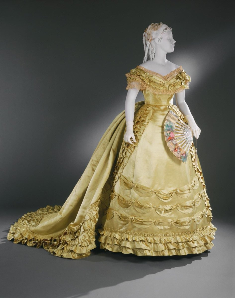 Designed by Charles Frederick Worth, English (active Paris), 1825 - 1895. Label Worth & Bobergh, Paris, 1857 - 1870 - essentially a layer cake made into a dress, but saffron yellow. Off the shoulder, typical mid-19th century Victorian design. From the PHL Museum of Art.