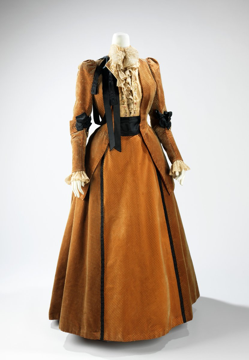 An orange afternoon gown in orange, fitted like a suit. Lace blouse with a jacket style bodice over a matching orange skirt, lightly flared. Black asymmetrical bow on the chest; black bow at waist, and at elbows. Met Museum, public domain.