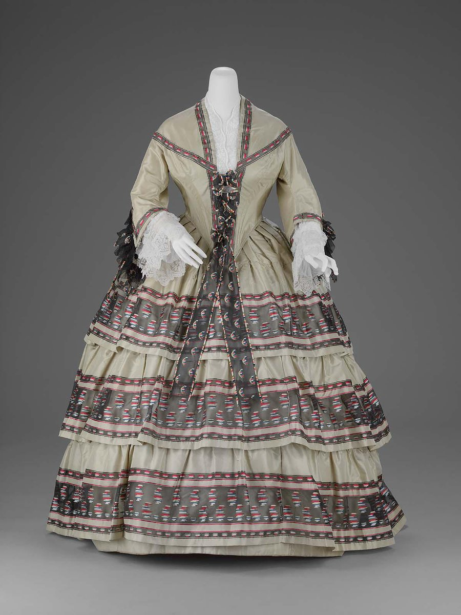 A dress in two parts, of light grayish green taffeta; (a) bodice fitted and boned, coming to deep point center front and back, elbow length bell shaped sleeves, hooked down center front, trimmed with bands of geometric motifs brocaded with red, white, and green silk on a sheer black silk ground, (woven in one with the gray-green taffeta as can be seen on the skirt ruffles), tabs to increase dimension of bodice, trimmed with brocaded black ribbon which has been added in center front, and similar ribbons combined with black net have been added at elbow of sleeves; (b) skirt very full with fullness pleated to waistband except at center back where it is gathered, three deep gathered flounces of the brocade on sheer black silk as described above around skirt; bodice lined with glazed white cotton, skirt lined with crinoline. Said to have been worn by the Parker ladies. Boston MFA.