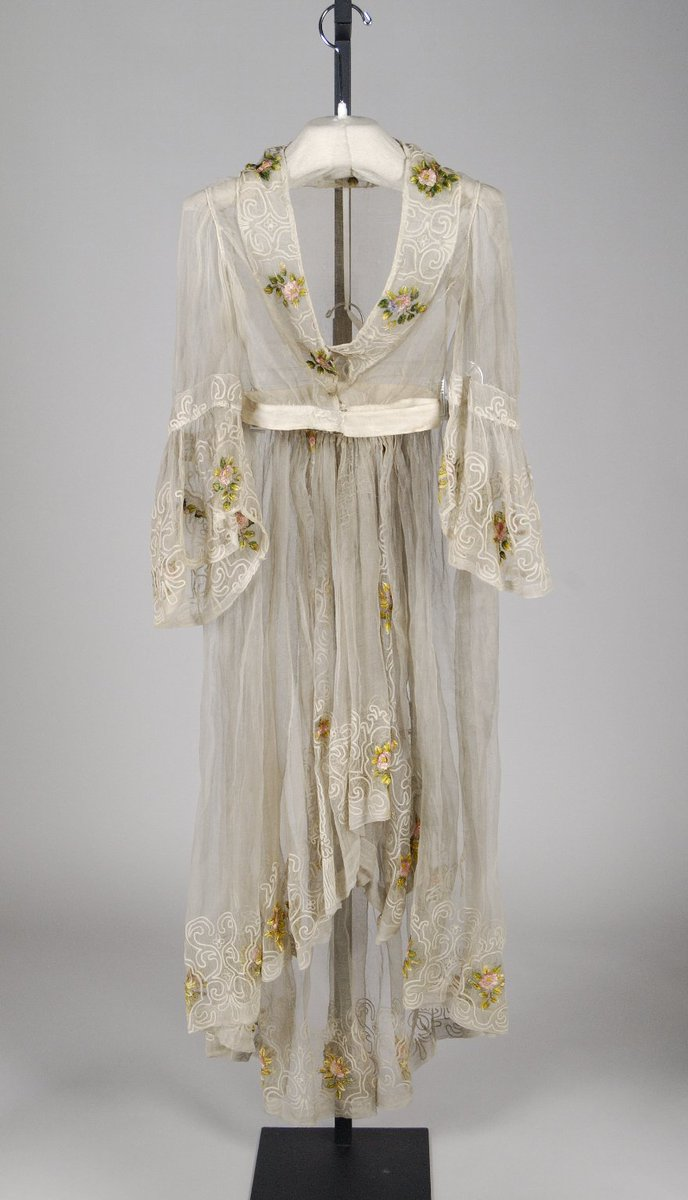 A dress from 1855, but not on a mannequin form. It looks like a sheer floral bathrobe. It has yellow flowers on it.  Met museum, public domain.