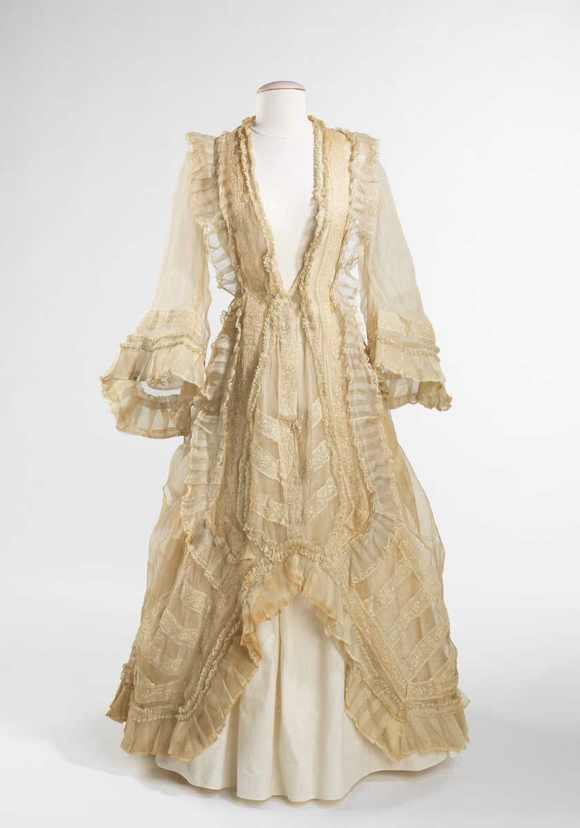 Dress with long bell sleeves, white underskirt, many pleats in off white. Deep v neck, likely to have another insert at some point. Met Museum.