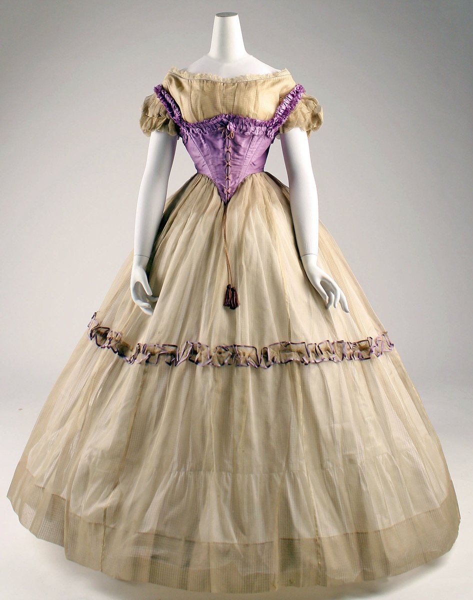 Princess style dress (think Rapunzel from Disney) -- bell-shaped gown, purple bodice, drop shoulder, puff sleeves. One ruched line down the center on the horizontal (sound weird, but that's what it is). Tassel from the waist V.