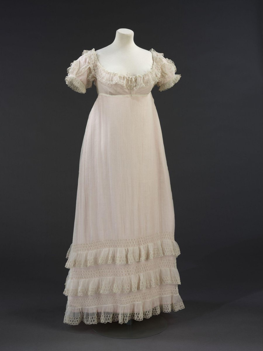 This sheer muslin evening dress demonstrates the survival of neo-classical elements of women's dress into the early 1820s. While heavier fabrics in brighter colours appeared in day dress, white remained fashionable for evening. This particular example may well have been for summer wear. It would have been worn with an under-dress of silk, possibly in coloured fabric. The off-the-shoulder neckline and short sleeves were appropriate evening styles. By the early 1820s, skirts shortened to ankle length and decorative flounces appear at the hem. ©Victoria and Albert Museum, London