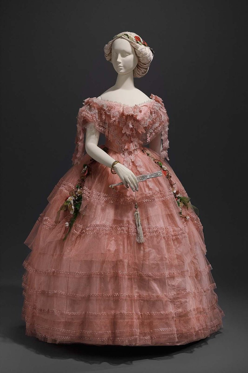 Bright pink tulle and taffeta dress; taffeta underdress; (a) bodice widely flaring neckline, short puffed sleeves, tightly fitted waist, sharply pointed center front and back, laced down back, trimmed with ruffles of blonde lace and bows of pink brocaded gauze ribbon, (b) skirt with five flounces trimmed with brocaded gauze, fullness evenly spaced all around, two garlands of artificial flowers tacked at sides of center front of skirt. - From BMFA, 1858, American or French