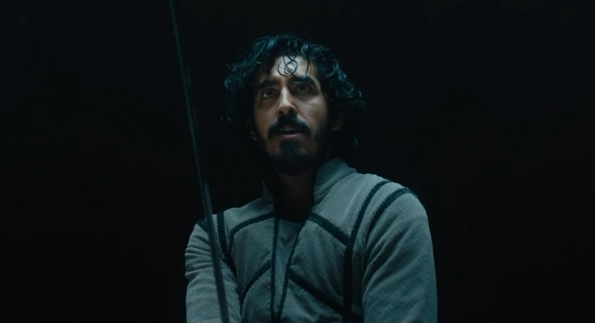 Dev Patel as Sir Gawain; in a grey doublet, holding a sword, looking up, against a black background.