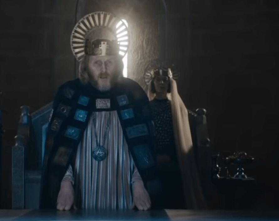 Sean Harris as the King in The Green Knight. He wears a crown that has a regular crown and then a HALO CROWN PIECE. He has a cloak with bits of embossed metal on it (like medals) and a chemise under, with a pentacle pendant.